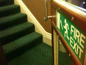 Fire exit sign pointing up stairs from 2nd floor of hotel