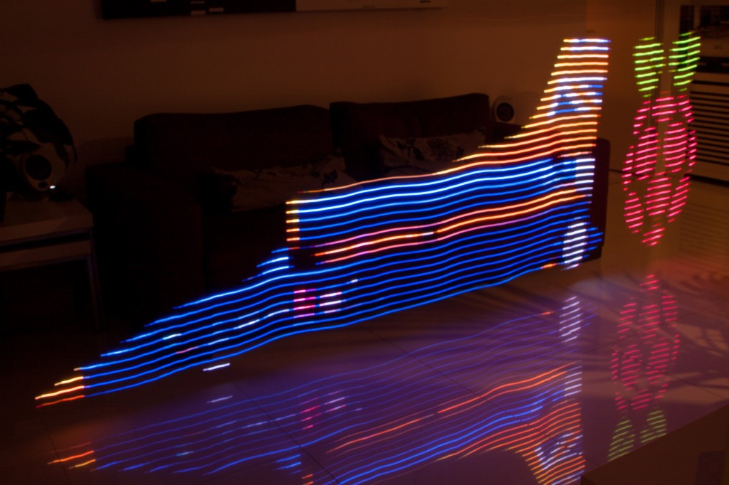 Long exposure light painting showing BloodhoundSSC car on left and Raspberry Pi logo on right